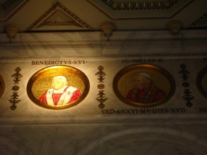 Pope Benedict XVI's bust illuminated, with Pope John Paul II's next to it.